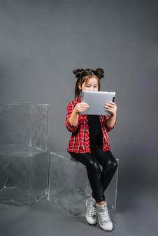 Ritratto di una ragazza che si siede sul blocco trasparente che esamina compressa digitale contro fondo grigio