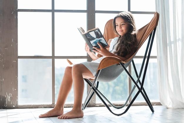 Ritratto di una ragazza che si siede sulla sedia vicino al libro di lettura della finestra