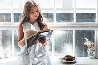 Ritratto di una ragazza che si siede vicino al libro di lettura della finestra