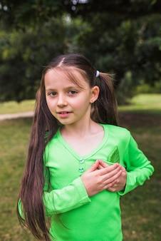 Ritratto di una ragazza con foglia verde falso in tasca