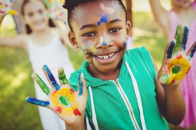 Ritratto di una ragazza con il trucco che le mostra le mani dipinte