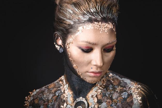 Ritratto di una ragazza con il trucco di pittura icona dorata
