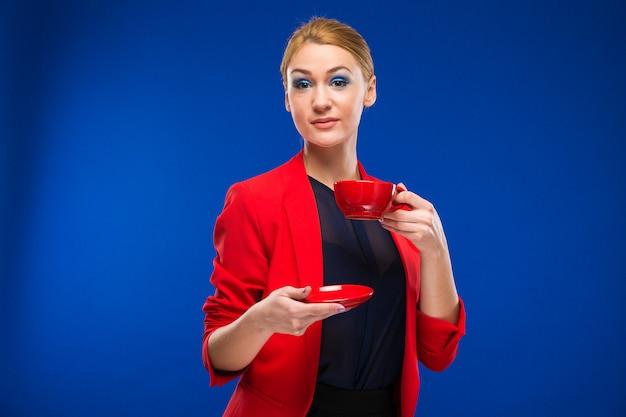 Ritratto di una ragazza con la tazza rossa nelle sue mani