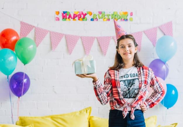 Ritratto di una ragazza con regalo di compleanno guardando la fotocamera