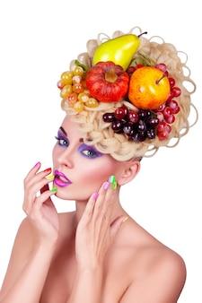 Ritratto di una ragazza con trucco e acconciatura professionali. frutta e verdura nei capelli