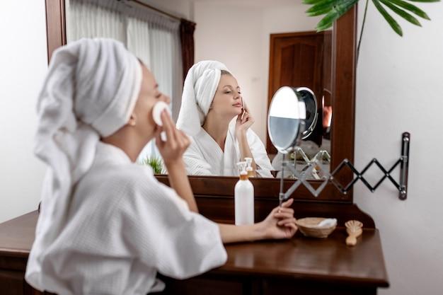 Ritratto di una ragazza con un asciugamano in testa e in un accappatoio bianco in posa e sorridente