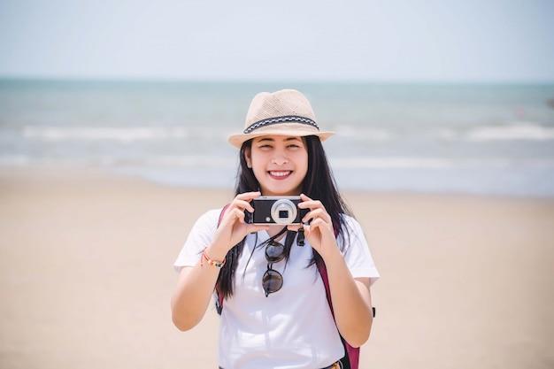 Ritratto di una ragazza con una macchina fotografica sulla spiaggia