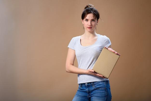 Ritratto di una ragazza con una scatola di cartone in mano su uno spazio beige
