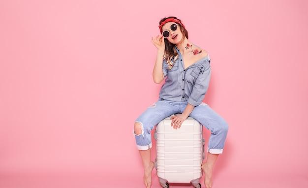 Ritratto di una ragazza con una valigia su uno sfondo rosa