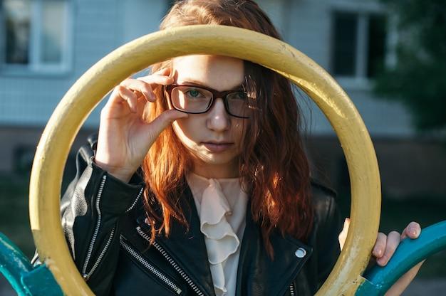 Ritratto di una ragazza dai capelli rossi con gli occhiali rossi in un parco giochi. la ragazza guarda attraverso il cerchio di ferro e regola i suoi occhiali.