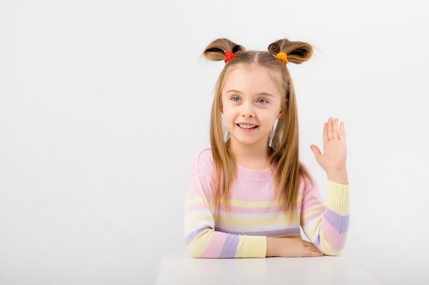 Ritratto di una ragazza del bambino che si siede ad uno scrittorio e che tiene la sua mano in su. spazio bianco, spazio per il testo
