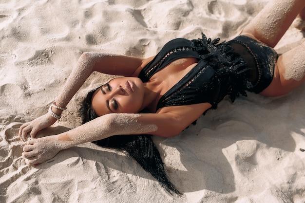 Ritratto di una ragazza di aspetto asiatico sdraiata sulla sabbia bianca con trucco luminoso e un costume da bagno in pizzo