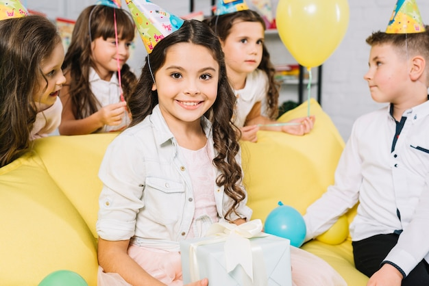 Ritratto di una ragazza di buon compleanno che tiene i regali nella mano seduto sul divano con i suoi amici