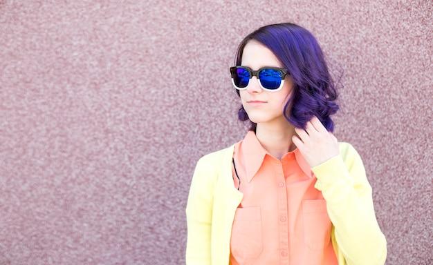 Ritratto di una ragazza di moda in occhiali da sole e capelli viola.