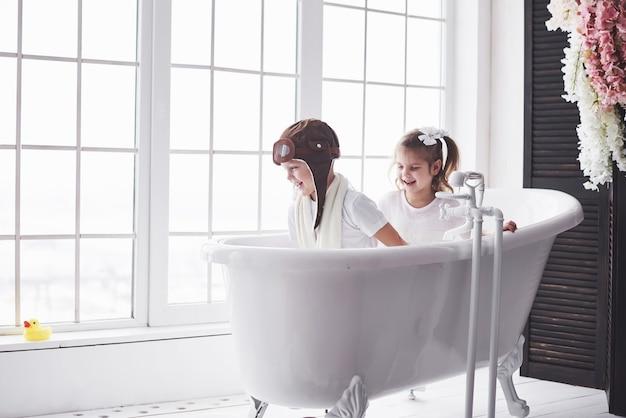 Ritratto di una ragazza e un ragazzo in cappello pilota che giocano nel bagno a piloti o marinai. il concetto di viaggio, infanzia e realizzazione dei sogni