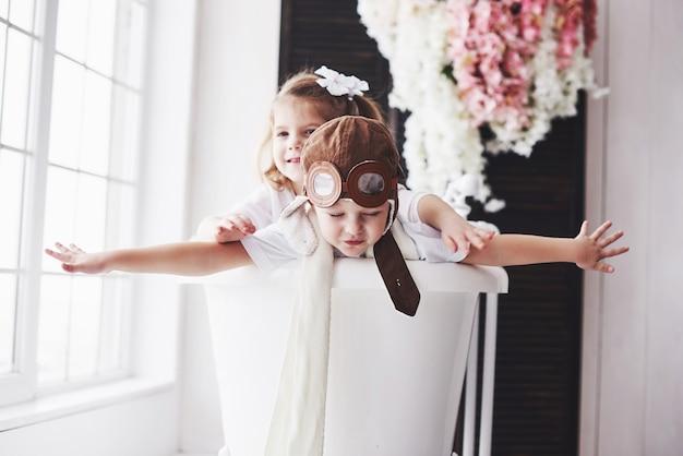 Ritratto di una ragazza e un ragazzo in cappello pilota che giocano nel bagno a piloti o marinai. viaggi, infanzia e realizzazione di sogni
