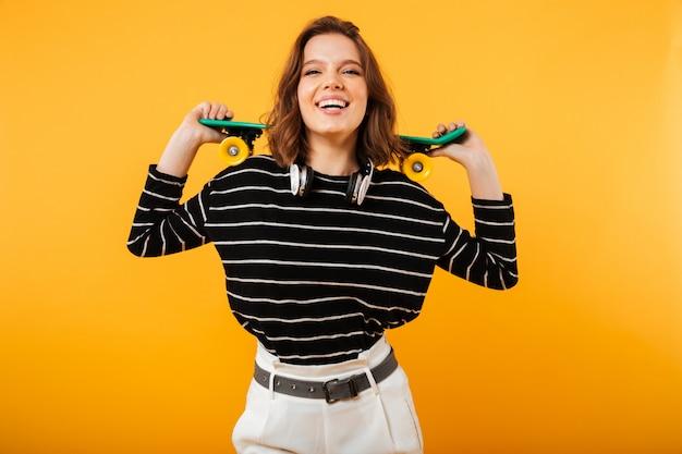 Ritratto di una ragazza eccitata tenendo lo skateboard sulle sue spalle
