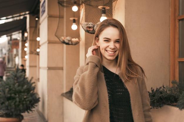 Ritratto di una ragazza felice che cammina per la città, in piedi vicino al muro marrone, indossando abiti caldi di primavera, guardando a porte chiuse e sorridente