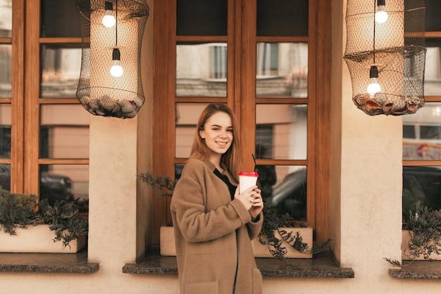 Ritratto di una ragazza felice in abiti primaverili in piedi sulla strada con una tazza di caffè in mano sullo sfondo di un muro marrone con finestre, guardando nella telecamera e sorridente