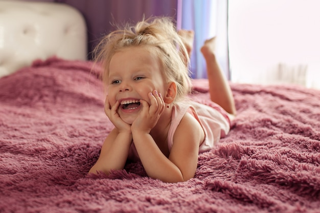 Ritratto di una ragazza felice sul letto