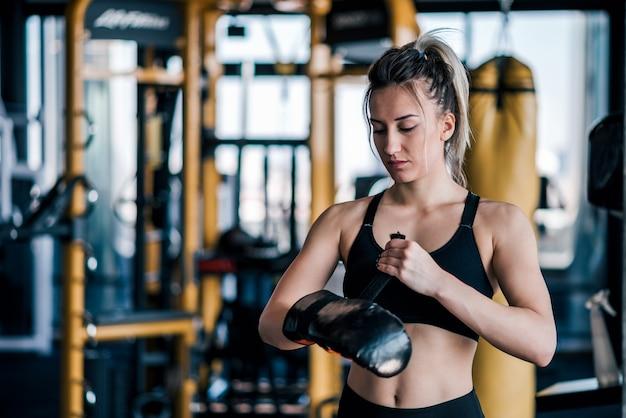 Ritratto di una ragazza giovane combattente preparando prima dell'allenamento.