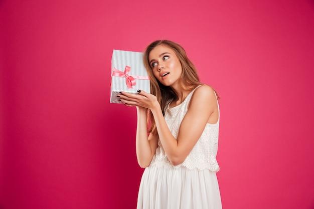 Ritratto di una ragazza graziosa che tiene il contenitore di regalo al suo orecchio