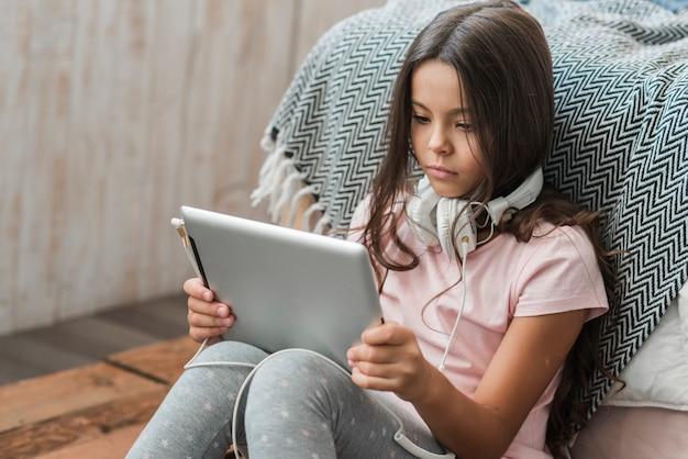 Ritratto di una ragazza guardando la tavoletta digitale con cuffia intorno al collo