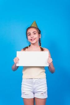 Ritratto di una ragazza in cappello di compleanno che mostra carta bianca in piedi su sfondo blu