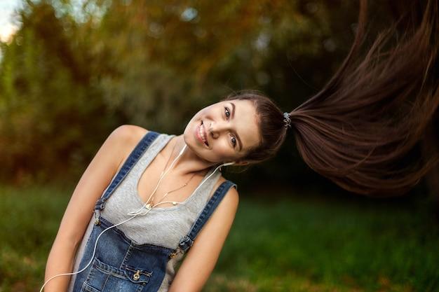 Ritratto di una ragazza in cuffia. sport e stile di vita sano, jogging per strada. capelli lunghi e sani, un'onda della sua testa, capelli volanti.