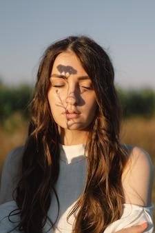 Ritratto di una ragazza in natura. bella ombra di fiori di campo sul viso della ragazza. un gioco di ombre.