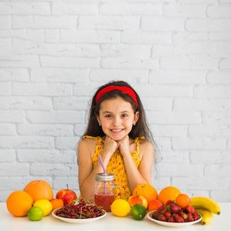 Ritratto di una ragazza in piedi dietro il tavolo con frutta fresca biologica