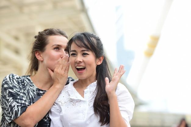 Ritratto di una ragazza pettegola che racconta un segreto nell'orecchio alla sua amica.