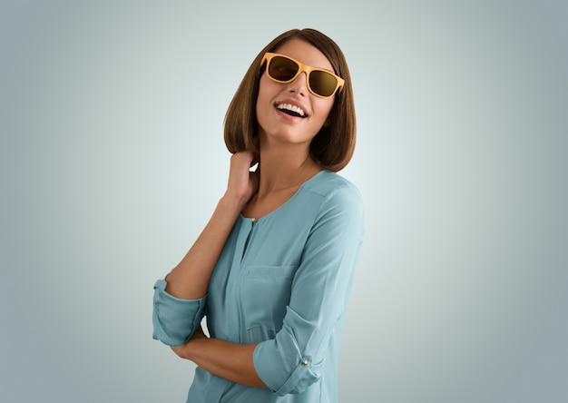 Ritratto di una ragazza positiva che indossa occhiali da sole