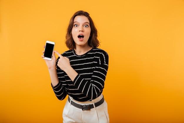 Ritratto di una ragazza scioccata che punta il dito