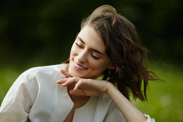 Ritratto di una ragazza seduta in un campo sull'erba primaverile tra i fiori di tarassaco.