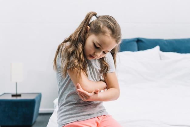 Ritratto di una ragazza seduta sul letto bianco guardando il suo gomito infortunato