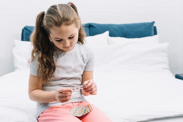 Ritratto di una ragazza seduta sul letto guardando le vesciche di pillole farmaceutiche
