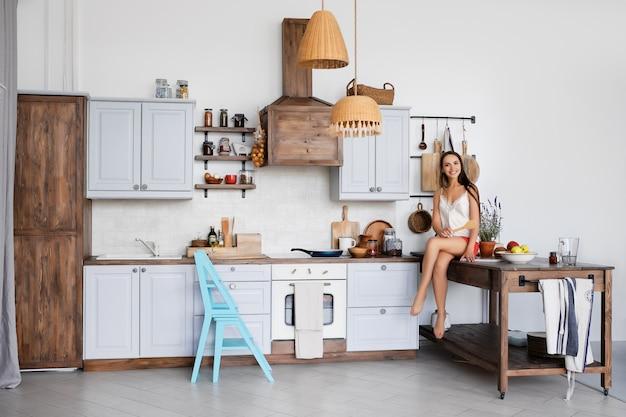 Ritratto di una ragazza seduta sul tavolo della cucina accanto alla stufa, cucina salsa in padella