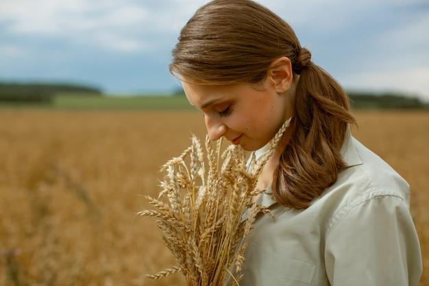 Ritratto di una ragazza slava di profilo con un mazzo di orecchie.