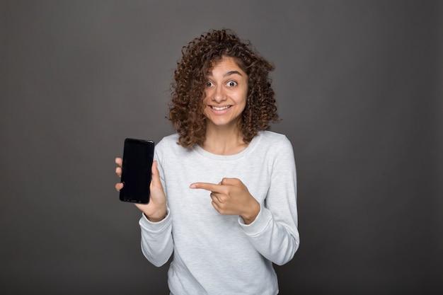 Ritratto di una ragazza sorpresa che punta il dito contro uno schermo di telefono cellulare vuoto.
