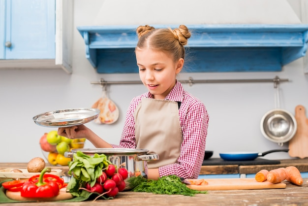 Ritratto di una ragazza sorridente che esamina l'acciaio inossidabile che cucina vaso nella cucina