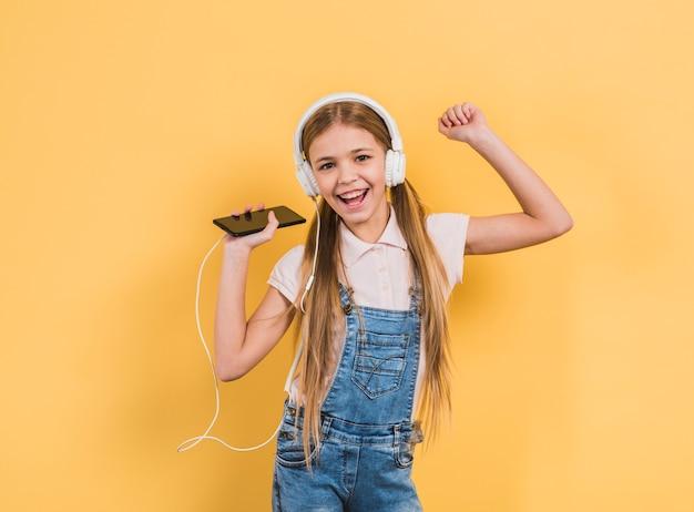 Ritratto di una ragazza sorridente che gode della musica sulla cuffia attraverso il dancing del telefono cellulare contro fondo giallo