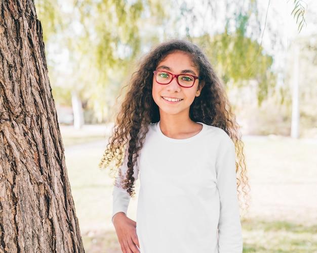 Ritratto di una ragazza sorridente che indossa occhiali rossi guardando la fotocamera