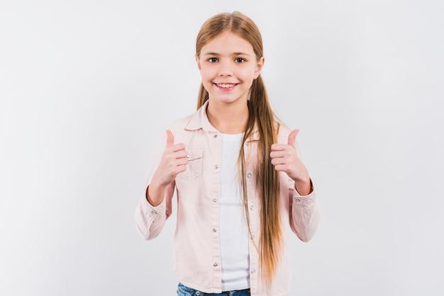 Ritratto di una ragazza sorridente che mostra pollice sul segno isolato su sfondo bianco