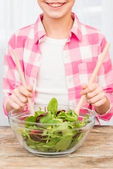 Ritratto di una ragazza sorridente che prepara insalata con il cucchiaio di legno nella ciotola di vetro