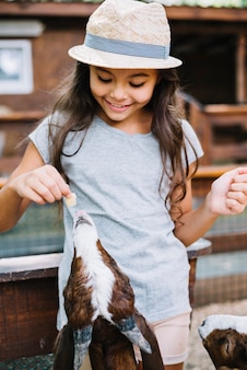 Ritratto di una ragazza sorridente che si alimenta alla capra
