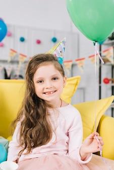 Ritratto di una ragazza sorridente che si siede sul divano con palloncino verde in mano