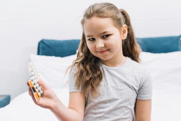 Ritratto di una ragazza sorridente che si siede sul letto che tiene medicina blister