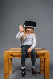 Ritratto di una ragazza sorridente che si siede sul tavolo con gli occhiali di realtà virtuale che toccano in aria
