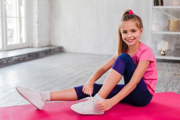Ritratto di una ragazza sorridente che si siede sulla stuoia di esercitazione che lega il suo laccio